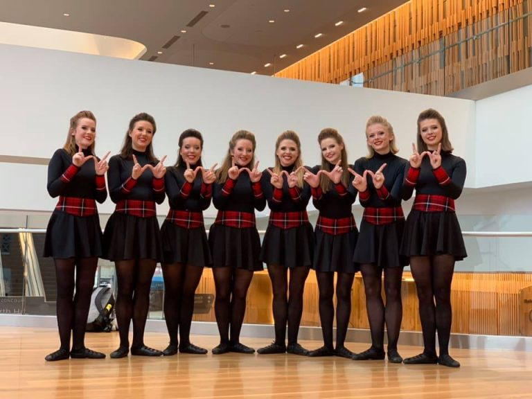 "Photo of the UW Irish Dance team standing in a row each holding up a ""W"" with their hands"