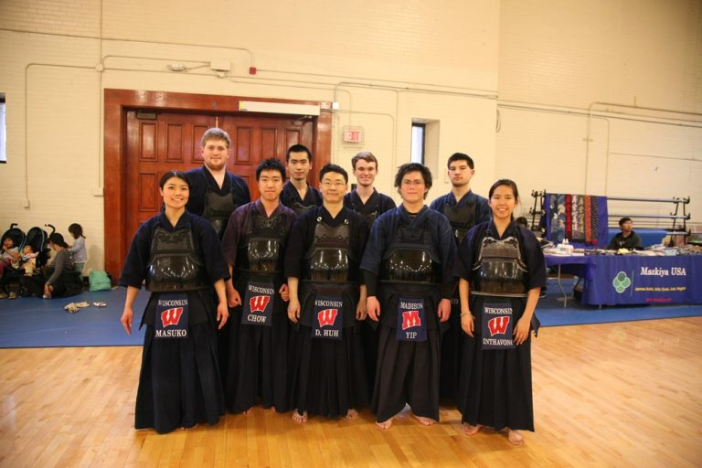 Photo of the UW Kendo team standing together in matching uniforms in an indoor gym