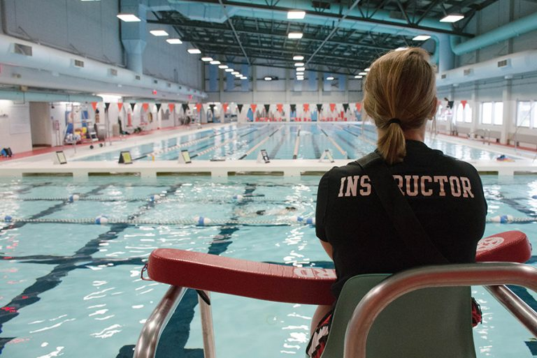 Photo of a female lifeguard sitting in a chair watching an indoor pool