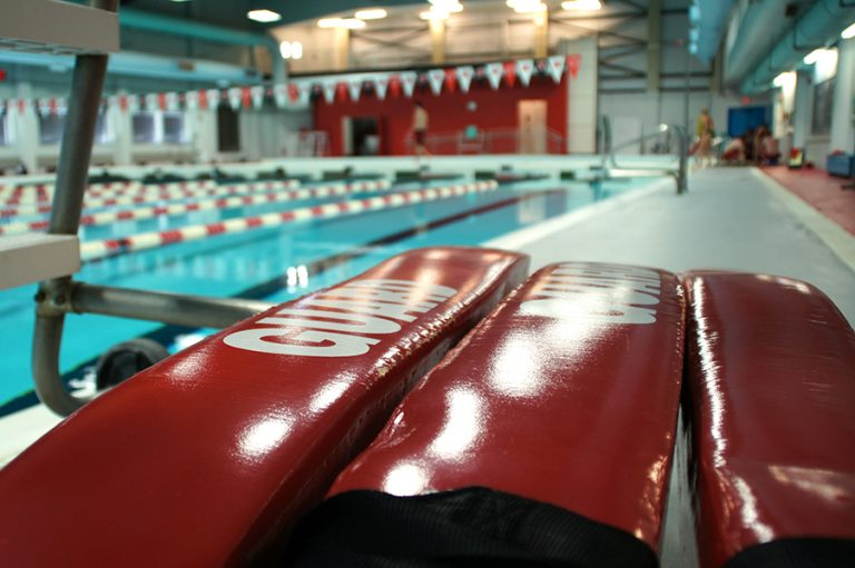 Photo of three red lifeguard buoys resting near an indoor pool