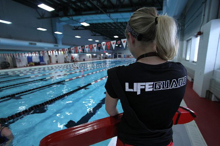 Photo of a female lifeguard standing next to an indoor pool