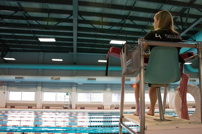 Photo of a female lifeguard sitting in a chair overlooking an indoor pool