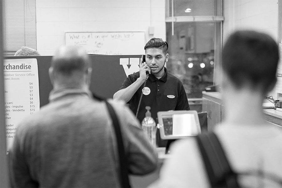 Black and white photo of student answering the phone in member services