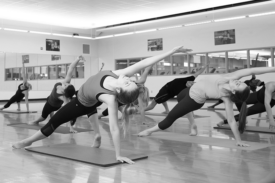 Black and white photo of a group of students performing a yoga pose in unison during an indoor group yoga class