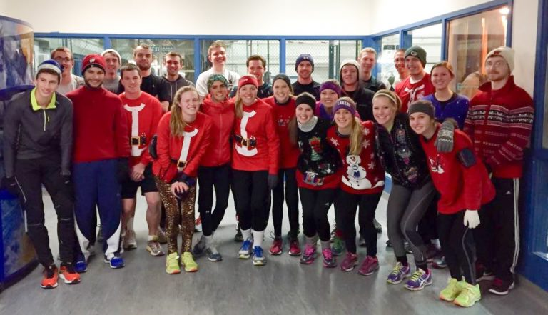 Photo of the UW Running Club standing together and wearing Christmas sweaters and running gear