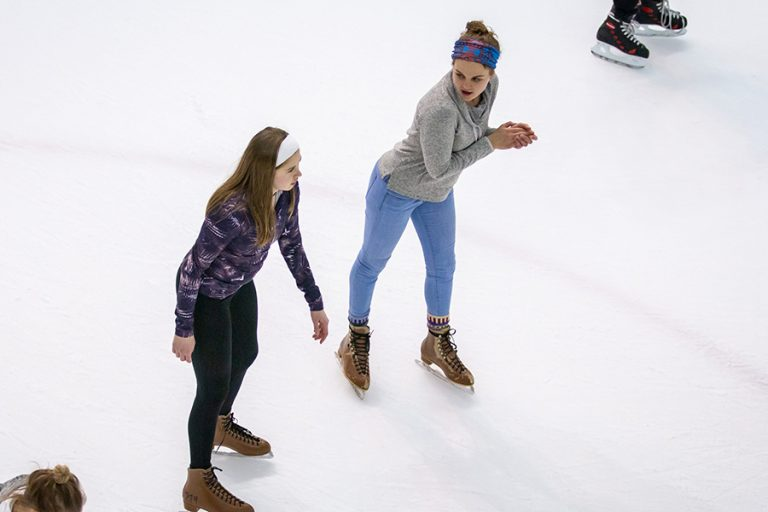 Photo of two women ice skating side by side on an indoor rink