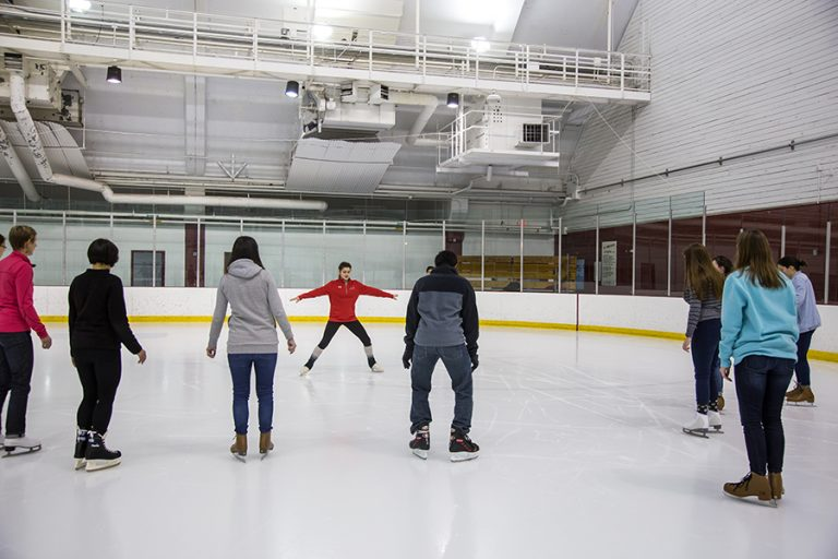 Photo of a skating instructor leading a skate lesson with her arms outstretched to her sides