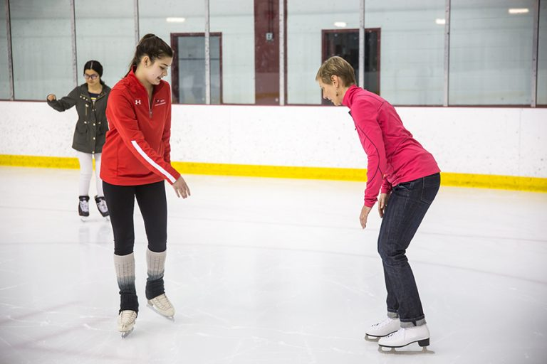 Photo of an ice skating instructor leading a woman as she learns to skate on an indoor rink
