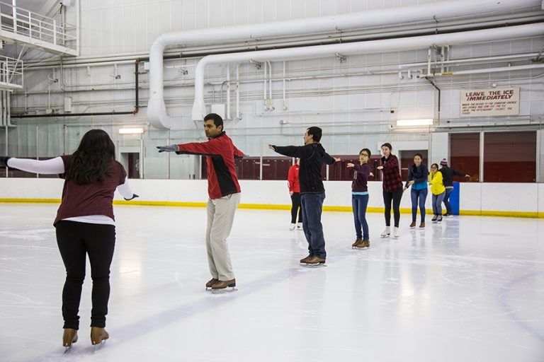 Photo of a group of ice skaters performing a spinning motion in a line during an ice skating lesson