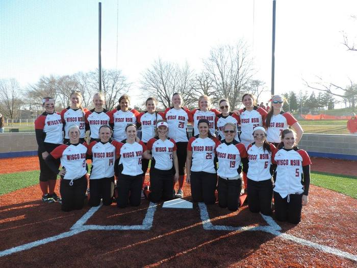 Photo of the UW Fastpitch Softball Team wearing matching uniforms posing at home base on an outdoor field