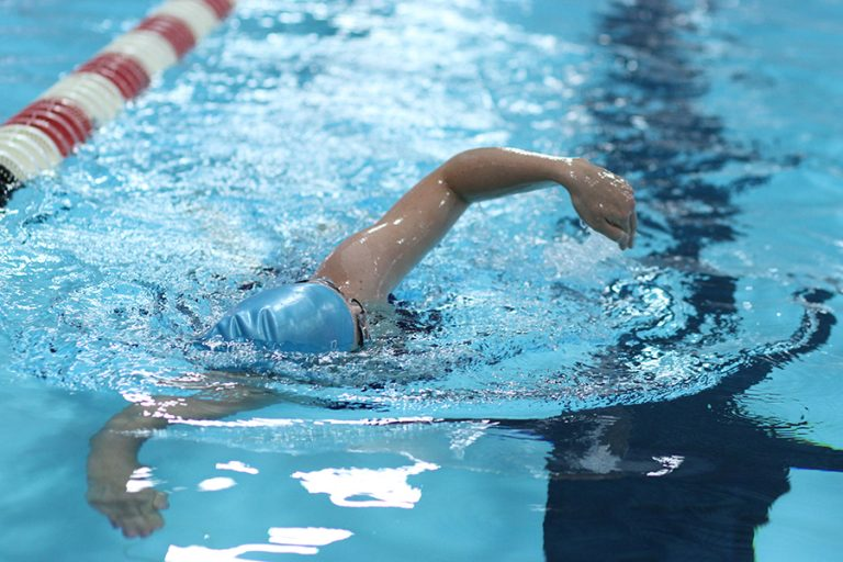 Photo of a person performing a front stroke in an indoor swimming pool lane