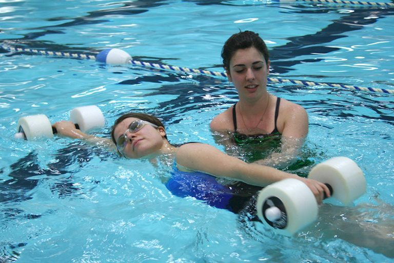 Photo of a swim instructor guiding a woman as she swims with floating dumbbells in her hands