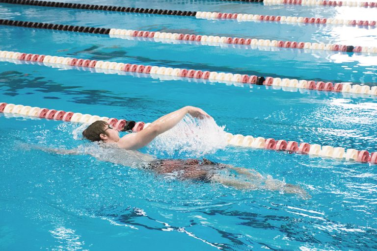 Photo of a man performing a front stroke in a lane in an indoor pool