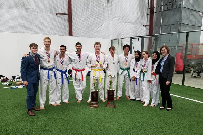 Photo of the UW Taekwondo club standing together next to two large trophies