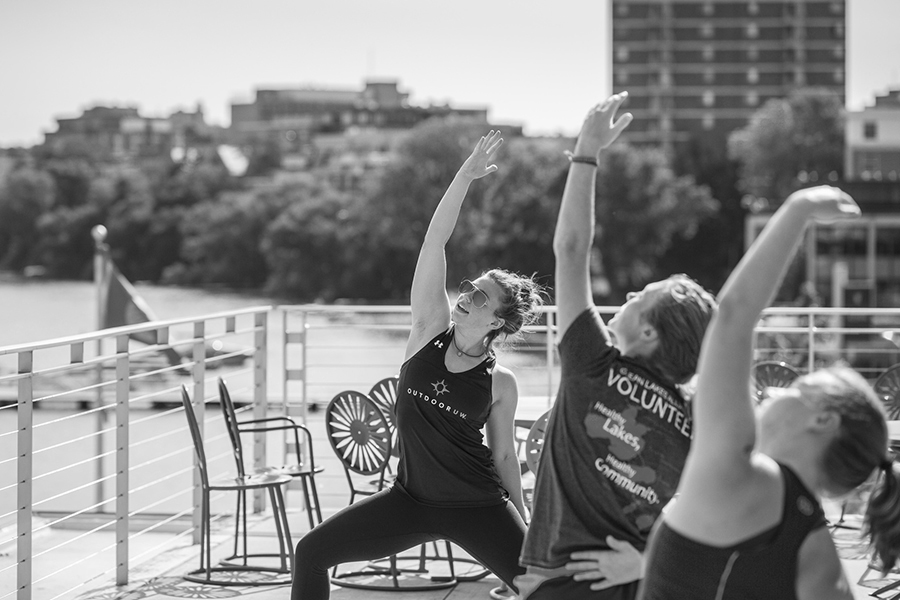 Black and white photo of three woman lunging with their arm outstretched above their head in sync on the Terrace by Lake Mendota
