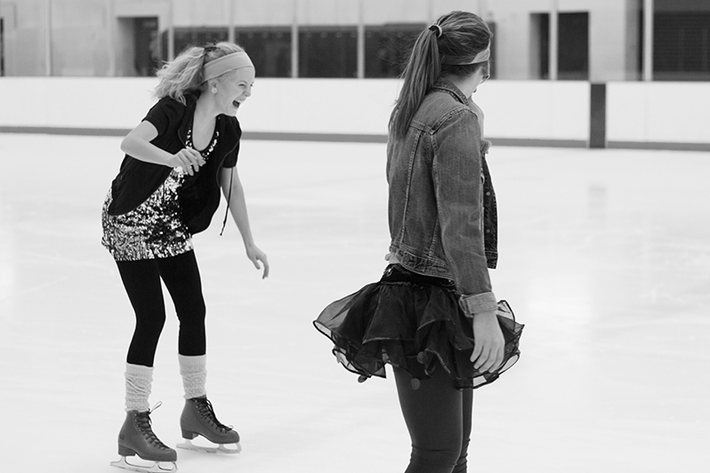 Photo of two girls skating on an indoor ice rink and wearing 80s costumes