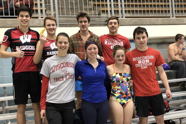 Photo of the UW Triathlon team standing on bleachers near an indoor pool