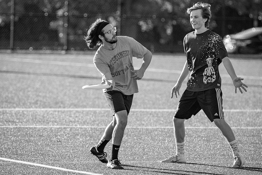 Black and white photo of an ultimate frisbee player throwing the frisbee as another player guards him
