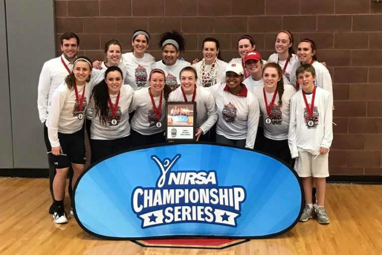 Photo of the Women's Basketball Club standing together with matching T-shirts and medals at the NIRSA Championship Series