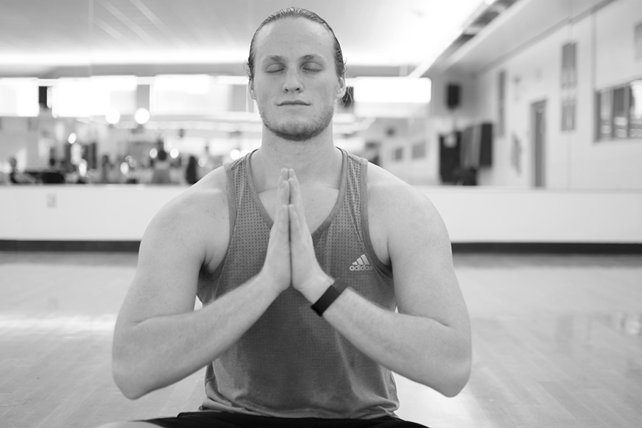 Black and white photo of a man sitting with his eyes closed and palms pressed together during an indoor yoga class