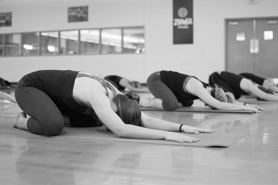 Black and white photo of a group of participants performing a downward-facing yoga pose on a mat in an indoor fitness studio