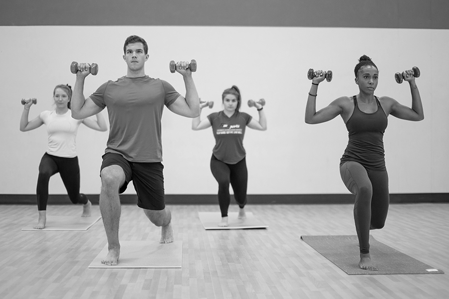Black and white photo of four fitness instructors lunging and holding weights in their hands together in an indoor fitness studio