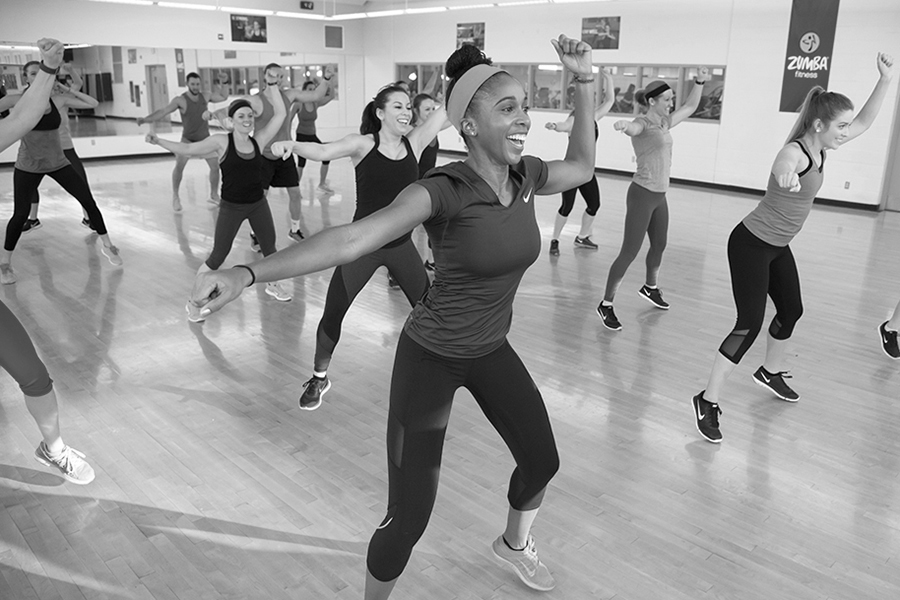Black and white photo of a group of participants performing a dance move in sync during an indoor Zumba class