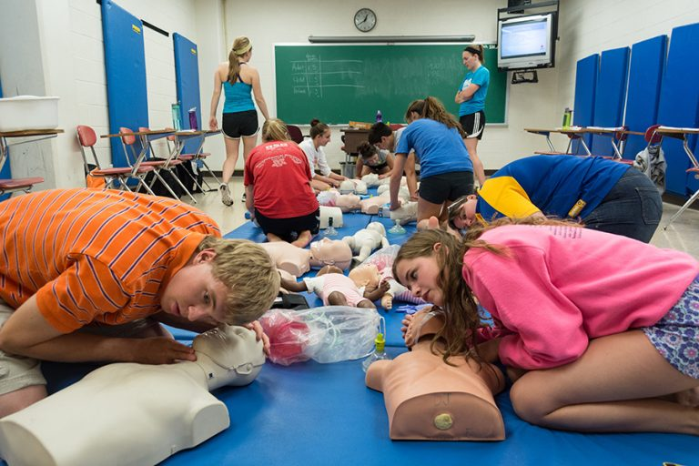 Photo of students crouched over near medical dummies during a CPR class in an indoor classroom.