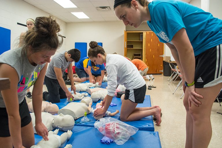 Photo of students practicing CPR on medical dummies on blue mats in a classroom.