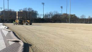 Photo of construction happening on the Near West fields as a machine smoothes the turf system