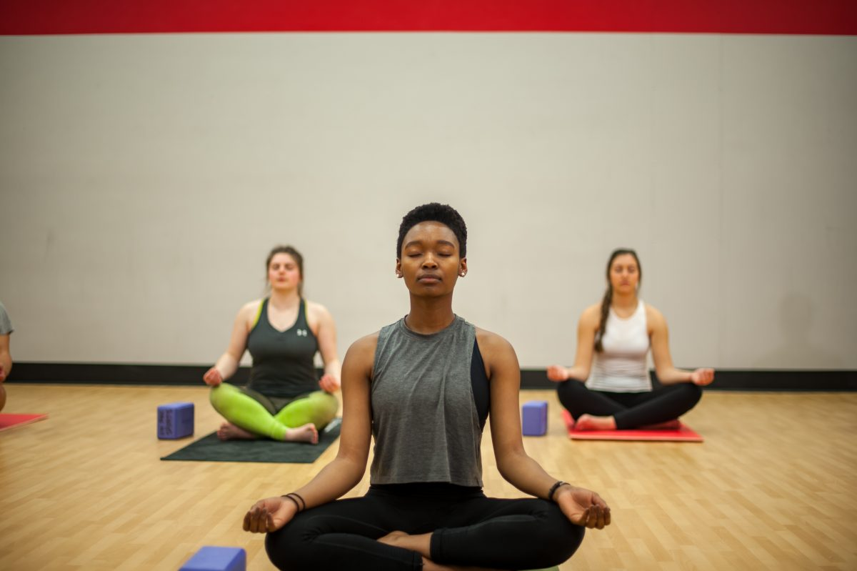 Photo of three fitness instructors sitting cross-legged on the ground with their eyes closed performing meditation in an indoor fitness studio.