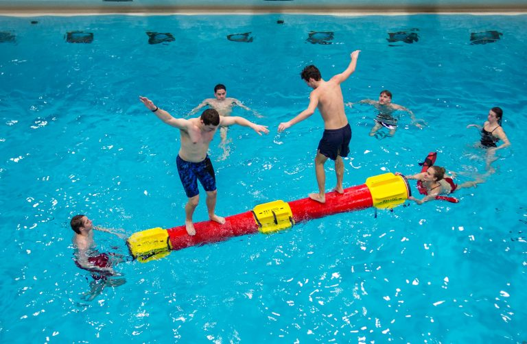 Photo of two young men standing next to each other on a foam log that is floating in an indoor pool. Two lifeguards and three students watch from the pool.