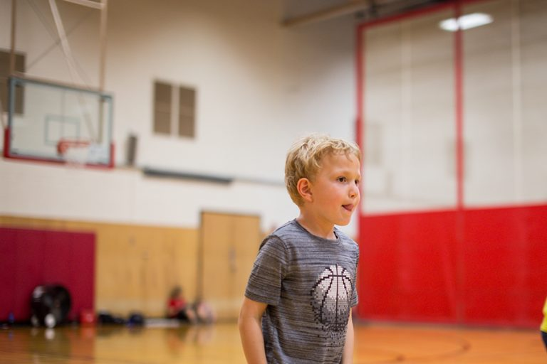 Photo of a young boy standing in an indoor basketball court sticking out his tongue.