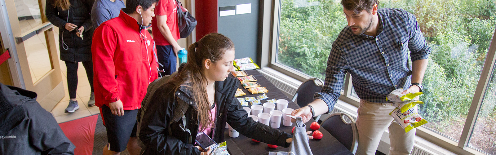 Photo of an employee handing a student a T shirt standing next to tables of free snacks and prizes.