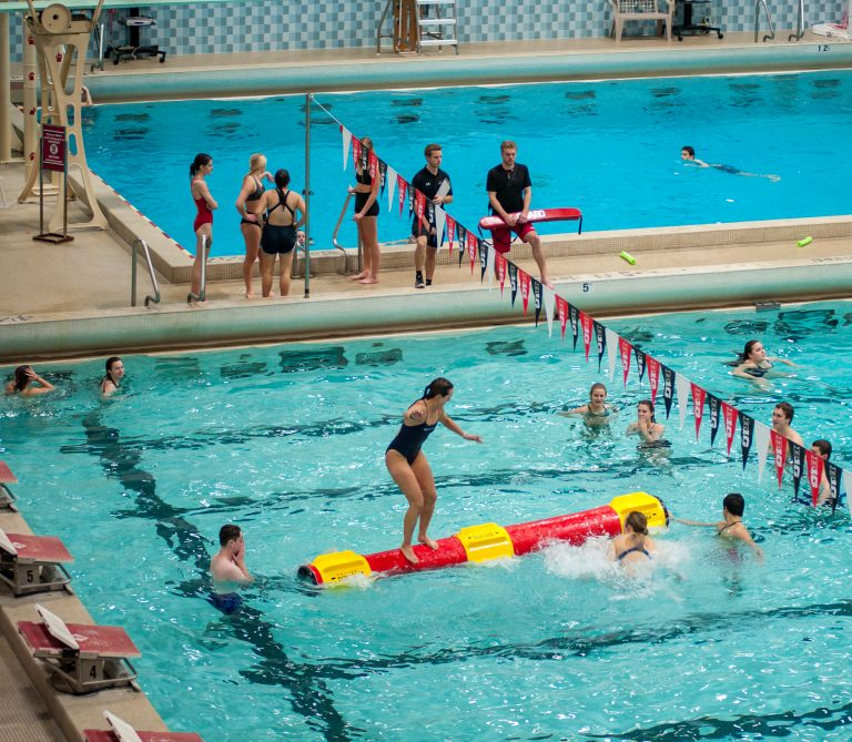 Photo of a young woman log rolling on a foam log at an indoor pool, surrounded by other students watching her from the water.