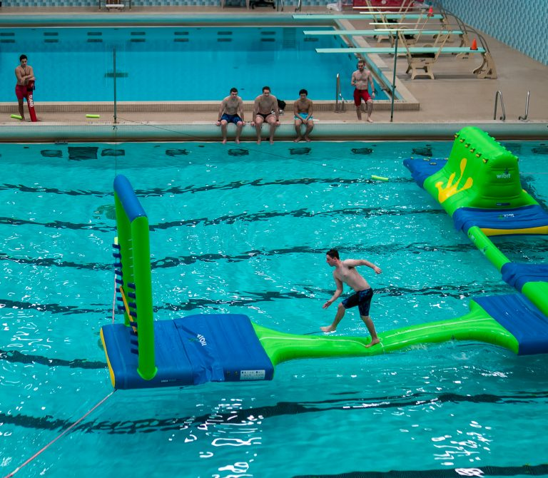 Photo of a young man running on a floating obstacle course in an indoor pool as four students and a lifeguard watch from the edge of the pool.