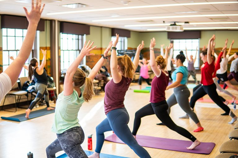Photo of a room full of women perform a lunging yoga pose in-sync with their arms in the air in an indoor fitness studio.