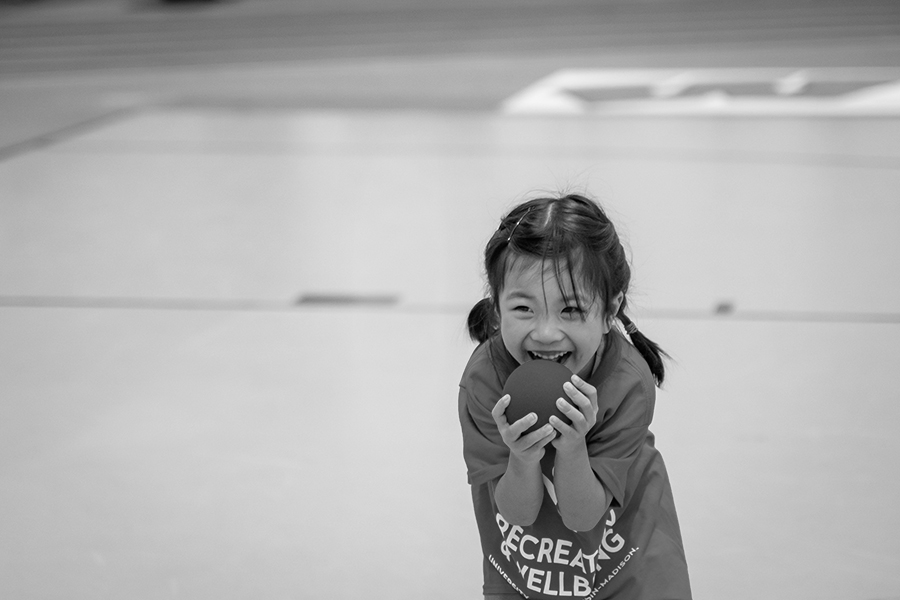 Black and white photo of a young girl grinning widely and holding a blue foam ball close to her face with both hands. She is wearing an oversized Rec Well T-shirt and is standing in a gymnasium