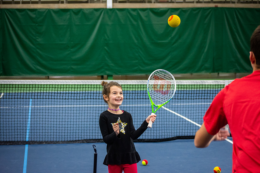 Photo of a smiling young girl holding up a tennis racquet and watching a tennis ball that is in the air moving towards her