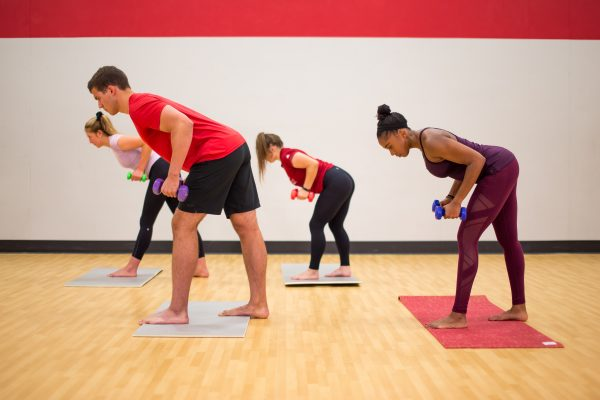 A photo of four group fitness instructors doing yoga with dumbbells in the Natatorium group fitness studio. The instructors are wearing bright red, purple, and black workout attire and standing on grey and red fitness mats.