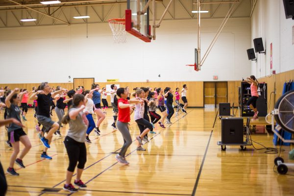 A photo of a full Zumba class in a brightly-lit Natatorium gym. Class participants are following the instructor at the front of the gym and jumping with their arms over their heads.