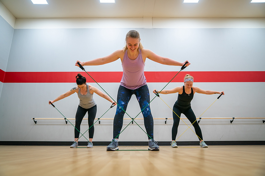 Photo of three smiling fitness instructors lifting their arms and stretching resistance bands in a cross motion while stepping down on the bands to hold them still. They are performing this exercise in a fitness studio with a wooden floor
