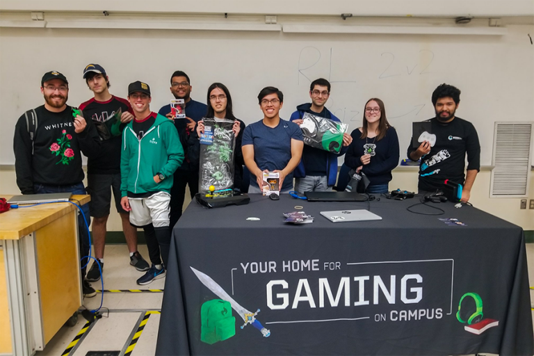 "A photo of students in a classroom holding gaming merch and standing behind a grey table with a tablecloth reading ""Your home for gaming on campus."""