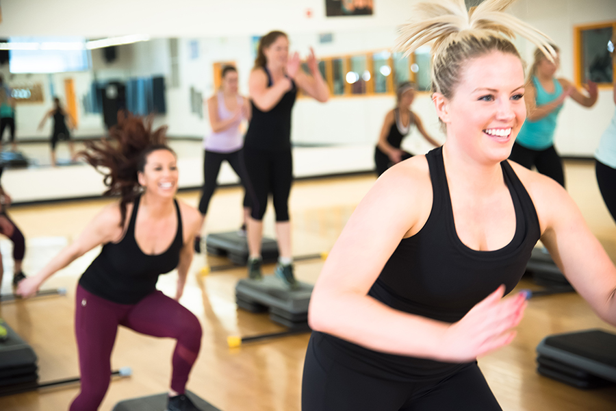 Photo of smiling fitness instructors jumping from stackable step platforms in a group fitness studio with a wooden floor