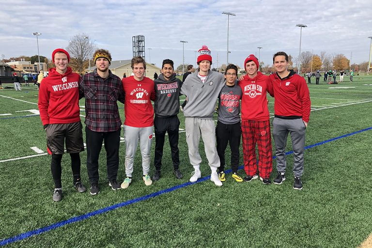 A photo of eight students wearing grey, red, and black UW-Madison shirts, sweatpants, and hats. The students are smiling and have their arms around each other.
