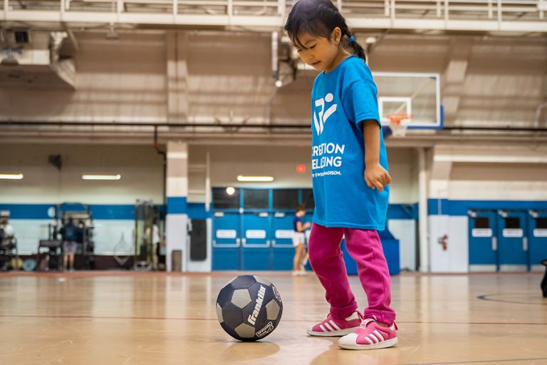 Photo of a young girl wearing an oversized Rec Well T-shirt dribbling a soccer ball in a gymnasium