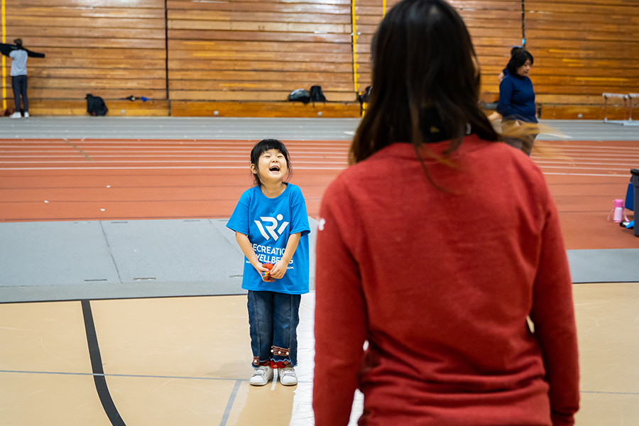 Photo of a young girl wearing an oversized Rec Well T-shirt and laughing. A woman stands in front of her with her back facing the camera.