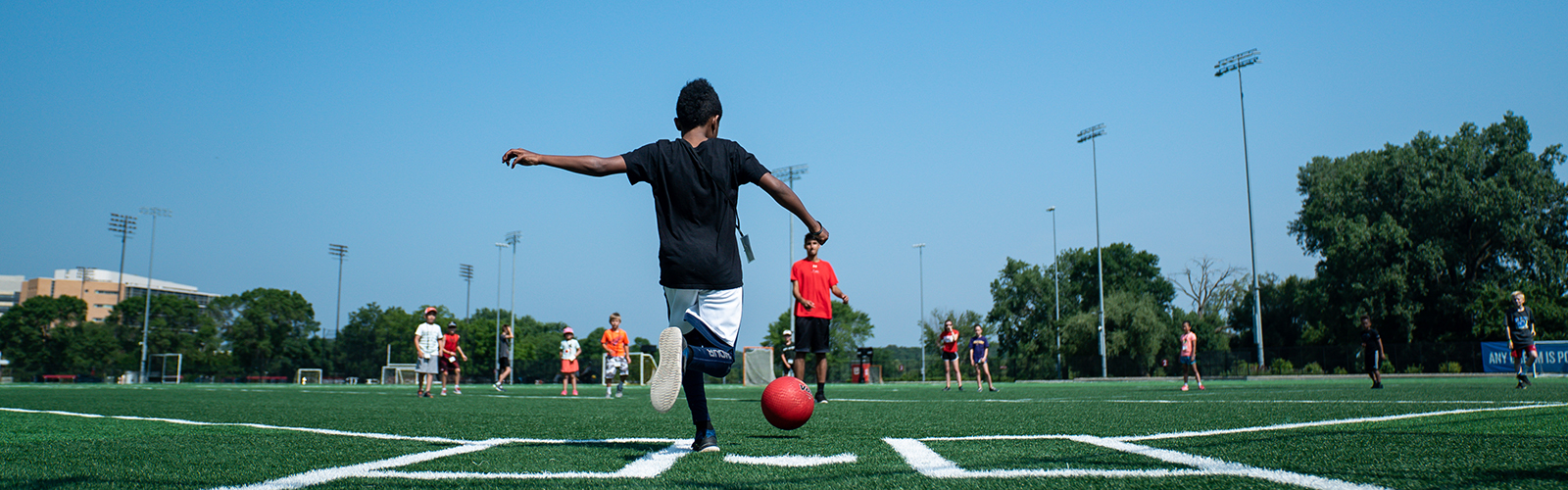 A photo of a child kicking a ball in a game of kickball.