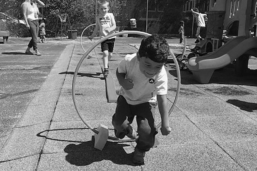 Black and white image of a young child smiling as he goes through a hoop on a playground.