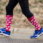 An image of a runner's legs, wearing red socks with motion W's on them.